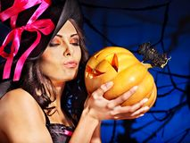 Witch holding pumpkin. Happy witch woman holding pumpkin Royalty Free Stock Image