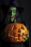 Witch holding a pumpkin Lantern. A witch holding a jack o lantern pumpkin royalty free stock photos