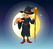 A witch holding a stick standing at the center of a full moon Stock Image