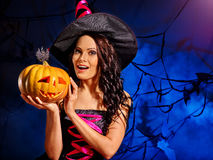 Witch keeps big orange Halloween pumpkin. Royalty Free Stock Photography