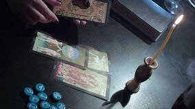 The witch lays out tarot cards. Conducts a spiritualistic session, looks at the future. Engaged in black magic