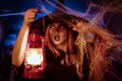 Witch With Lighted Lantern. In her hand in creepy cobweb surroundings is looking for saomething Royalty Free Stock Photos