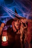 Witch With Lighted Lantern. In her hand in creepy cobweb surroundings is looking for saomething Stock Image
