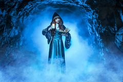 The witch with magic ball in her hands causes a spirits. In cave stock image