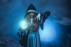 The witch with magic ball in her hands causes a spirits. In cave royalty free stock photo