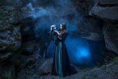 The witch with magic ball in her hands causes a spirits. In cave stock photos