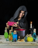 Witch with magic bottles and pot Stock Photography