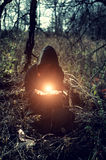 Witch with magic fire. In the dark forest Stock Photo