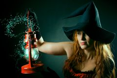 Witch with the magic lantern. Pretty redhead witch in red corset with shiny red lantern  posing over dark background Stock Photo