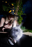 Witch with magic sphere. Witch holding glowing moon and telling the spell royalty free stock photos