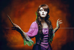 Witch and the magic wand. Witch casts a spell with a magic wand for halloween Royalty Free Stock Photography