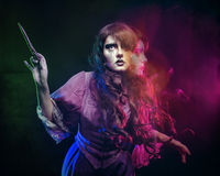 Witch and the magic wand. Girl in the image of a witch with a magic wand shot in studio Stock Photography