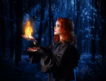 Witch in the moonlight forest with flame Royalty Free Stock Photo