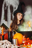 Witch near the boiler with book Royalty Free Stock Images
