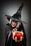 Witch offering a poisoned apple. Closeup of a spooky witch offering a poisoned apple Royalty Free Stock Photography