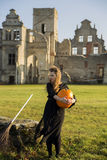 Witch with pale skin embraces pumpkin Royalty Free Stock Photography