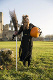 Witch with pale skin hold broom Royalty Free Stock Image