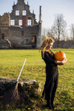 Witch with pale skin look at pumpkin Royalty Free Stock Photos