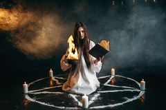Witch in pentagram circle, dark magic ritual. Witch in white shirt sitting in the center of pentagram circle with candles, dark magic ritual process. Occultism Stock Photo