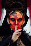Witch portrait in black vintage dress. Woman widow with red art make-up for halloween. Face like Victorian-Mask. Index finger at the lips. Quiet. Professional Stock Photos
