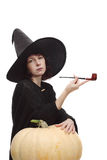 Witch posing with a pipe Royalty Free Stock Photo