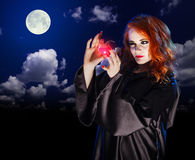 Witch with potion on night sky background Royalty Free Stock Photos