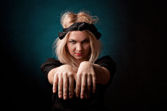 Witch  practises witchcraft on black background. Stock Photo
