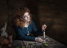 Witch preparing potion. The red-haired witch preparing a potion from a variety of ingredients, spread on a wooden table. Picture toned Stock Image