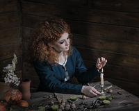 Witch preparing potion. The red-haired witch preparing a potion from a variety of ingredients, spread on a wooden table. Picture toned Stock Images