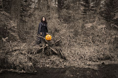 Witch with pumpkin in the forest Royalty Free Stock Image