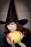 Witch with pumpkin in hands Stock Photo
