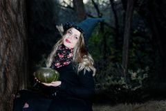 A witch with a pumpkin in his hands. In the forest. Witchcraft Halloween Stock Photos