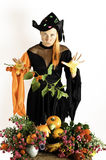 Witch and pumpkins and flowers Royalty Free Stock Photography