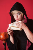 Witch Reads a Scroll. Hooded witch over red background reads a scroll Royalty Free Stock Photos