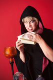Witch Reciting Spells. Evil witch reciting spells from a scroll Stock Images