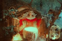 Witch in a red dress with bare shoulders of the Baroque era, is preparing a poison. The sorceress calls upon the powers. Witch in a red dress with bare shoulders royalty free stock photo