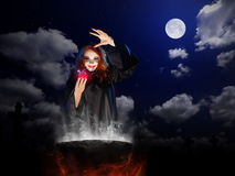 Witch with red potion and cauldron  at night sky backgroun Royalty Free Stock Photography