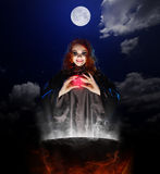 Witch with red potion and cauldron on night sky background Stock Photos
