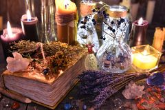 Witch ritual collection with old spelling book, lavender, bottles, herbs and magic objects. Occult, esoteric, divination and wicca concept. Halloween background Royalty Free Stock Image