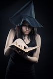 Witch's Apprentice. Pretty young girl in witch hat reading spell book over dark background Stock Photography