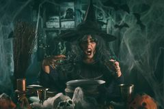Witch Sends Evil Makes. Witch with awfully face and hat on her head in creepy surroundings full of cobweb sends evil Royalty Free Stock Photo