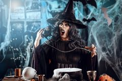 Witch Sends Evil Makes. Witch with awfully face in creepy surroundings full of cobweb with blackbird on her shoulder sends evil thoughts Royalty Free Stock Image