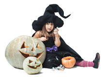 Witch sits near the pumpkins and eating candy Stock Photo