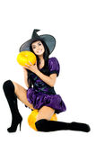 Witch sitting on a pumpkin. Very sexy young brunette witch sitting on a pumpkin and holding pumpkin Stock Images