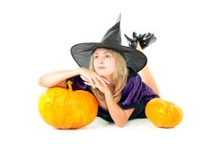 Witch sitting beside pumpkins Stock Images