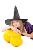 Witch sitting beside pumpkins Royalty Free Stock Image