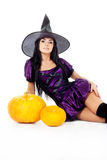 Witch sitting beside pumpkins Stock Photo
