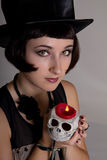 Witch with a skull in a black cylinder hat Royalty Free Stock Photos