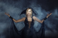 Witch in the smoke. Angry lady in witch costume conjuring in the smoke Stock Photo
