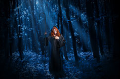 Witch with staff in night forest Royalty Free Stock Photos